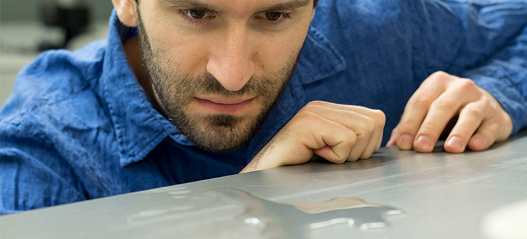 Engineering Assistant Professor Kevin Golovin observes water pooling on a superhydrophobic surface.